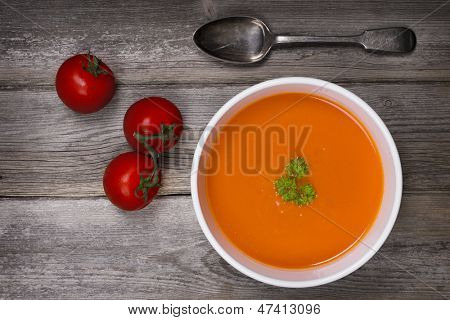 A bowl of tomato soup with a tarnished silver spoon and fresh vine tomatoes, against a rustic wood tabletop. Vintage style with intentional vignette and selective desaturation