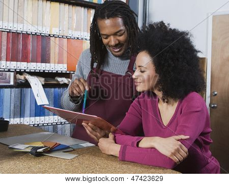 Young woman and flooring sales clerk looking at clipboard