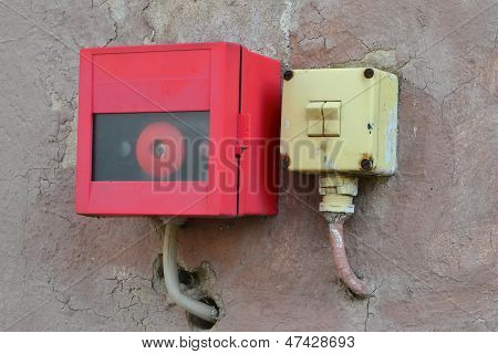 an old light switch and an alarm button on a house wall