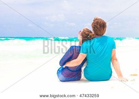 youn happy couple looking on horizon on beach