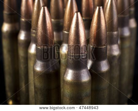 Rifle Bullets closeup on isolated  black backgrounds poster