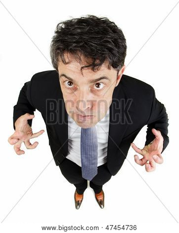 Fun high angle portrait with diminishing perspective of a frustrated angry man glowering up at the camera while making claws of his hands, isolated on white