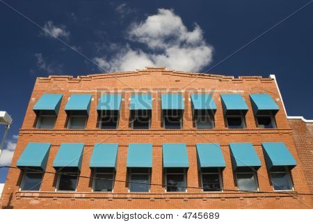 A red brick building with two rows of teal window shades against a blue sky with white fluffy clouds. poster
