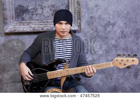 Young man in striped vest and knitted jacket sits with guitar near grey scuffed wall