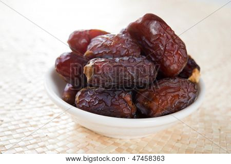 Kurma dried date palm fruits, ramadan food which eaten in fasting month. Pile of fresh dried date fruits in bowl.