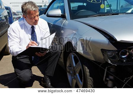 Loss Adjuster Inspecting Car Involved In Accident
