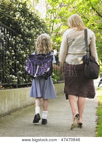 Rear view of schoolgirl walking with mother on pavement