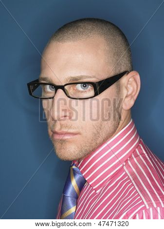Portrait of a serious bald man in glasses against blue background