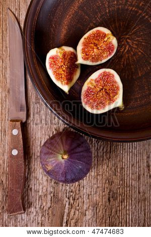 bowl with fresh figs and old knife on rustic wooden table