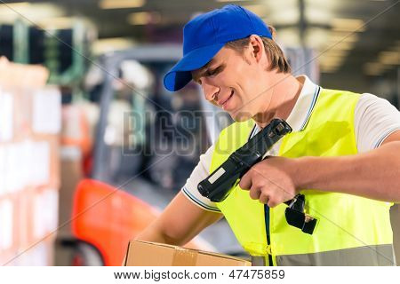 Warehouseman with protective vest and scanner, scans bar-code of package, he standing at warehouse of freight forwarding company