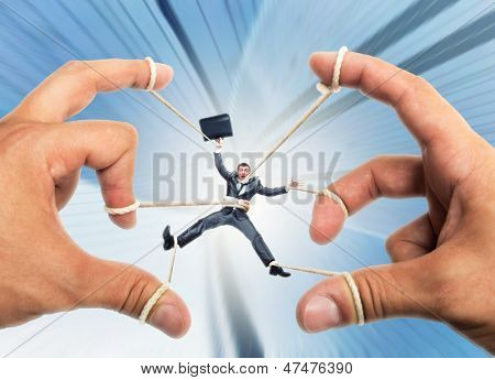 Stressed businessman governed by puppeteer hands poster
