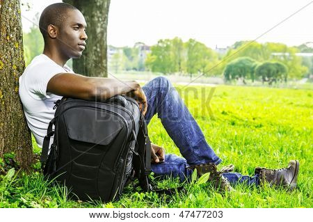 Young african american man in white shirt  with rucksack in a park