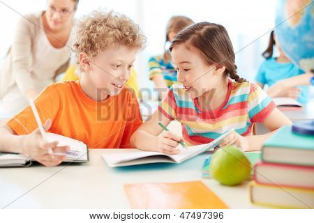 Portrait of two diligent pupils interacting while drawing at lesson