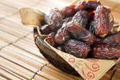 Dried date palm fruits or kurma, ramadan food which eaten in fasting month. Pile of fresh dried date fruits ready to eat in bamboo basket. poster
