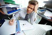 Perplexed accountant looking at camera while doing financial reports poster
