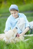 Portrait of cute lad cuddling his fluffy friend while lying on grass poster