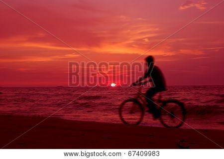 Active. Cyclist on the beach at sundown. poster