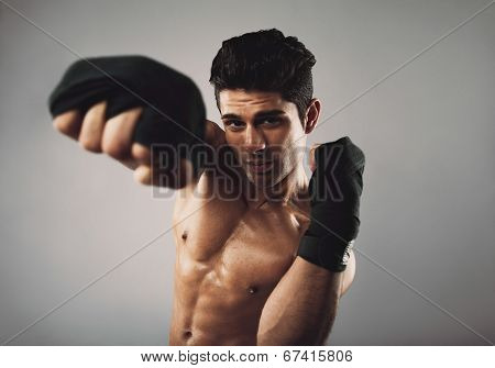 Portrait of strong young man wearing boxing gloves practicing shadow boxing. Health and fitness theme on grey background. poster