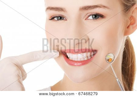 Young doctor or dentist with dental mirror and glove pointing on teeth. Isolated on white.