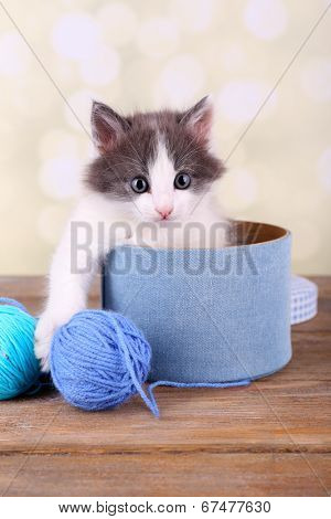 Cute little kitten in box playing with thread ball, on light background poster