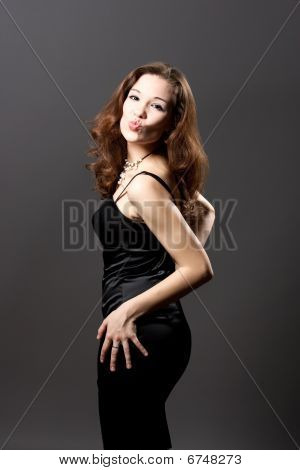extravagant young caucasina girl in black evening dress with kiss
