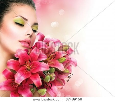 Beauty Girl with Lilly Flowers bouquet. Beautiful Model woman with Blooming pink lily flowers. Nature. Summer. Holiday Creative Makeup. Fashion Make up. Spa woman Portrait