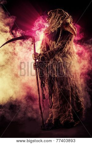Portrait of a terrible plague doctor with a scythe. Medieval Europe. Horror. Halloween.