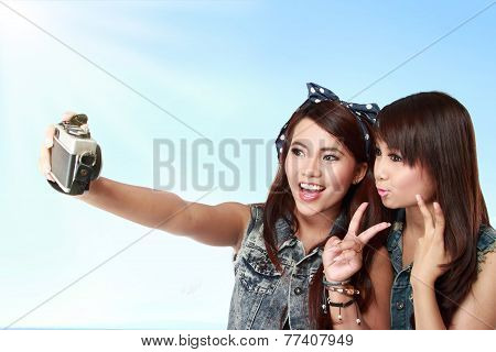two happy woman take a photo of her self. selfie portrait poster