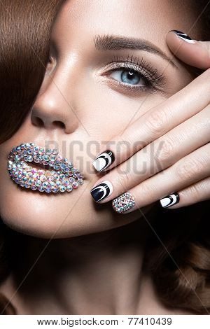 Beautiful girl with bright nails and lips of crystals, long eyelashes and curls. Beauty face.