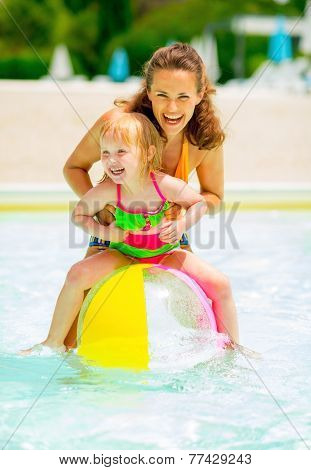 Portrait Of Happy Mother And Baby Girl Playing With Beach Ball I