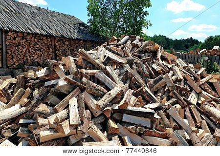 Old firewood shed and a lot of chopped logs in Belarus poster