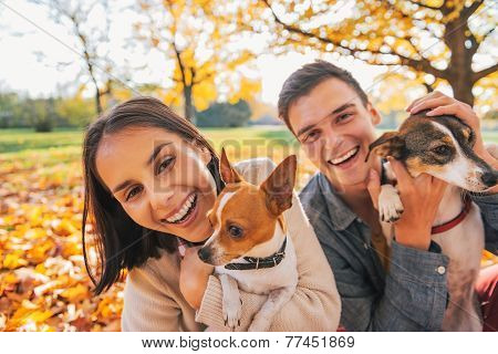 Portrait Of Smiling Young Couple With Dogs Outdoors In Autumn Pa