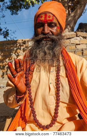 JAISALMER, INDIA - NOVEMBER 28, 2012: Indian sadhu (holy man) blessing. Sadhus are holy men who live ascetic life and focus on spiritual practice of Hinduism