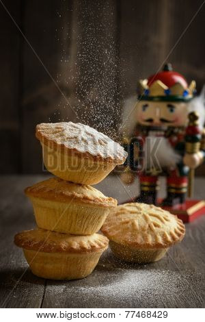Dusting mince pies with icing sugar for Christmas