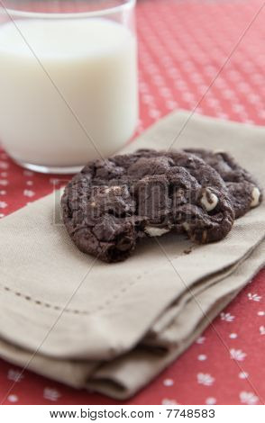 Chocolate Cookies On A Napkin With A Glass Of Milk