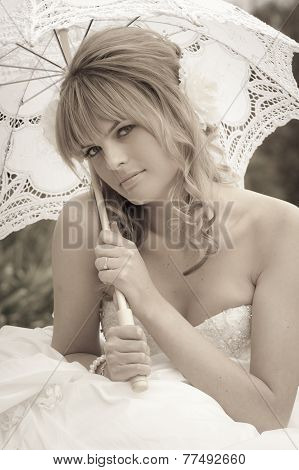 Young beautiful bride sitting outdoors in wedding dress