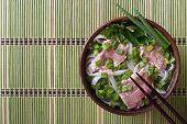 Vietnamese Pho Bo soup with beef rare rice noodles and fresh herbs closeup. top view of a horizontal poster