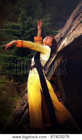 A beautiful girl in a historical costume posing in a dramatic gesture amids the forest surroundings