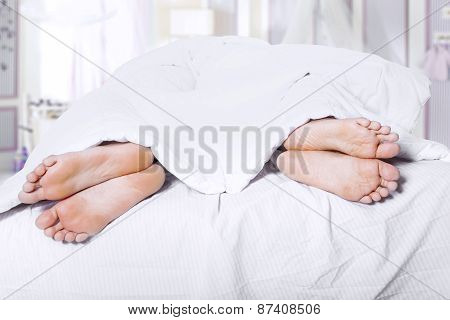 Two Pair Of Feet On Bed