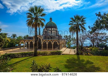 The dome of basilica is surrounded by a gallery. Church Sermon on the Mount - Mount of Beatitudes. Subtle shade of palms and cypresses