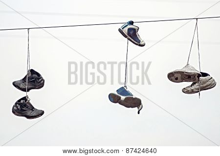 Three Couples Old Sneakers On Wires
