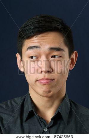 Young Asian man rising eyebrows and looking sideways