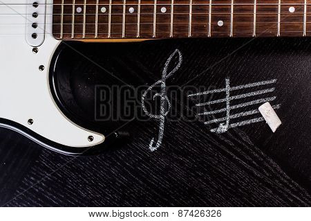 black electric guitar and treble clef on dark table.