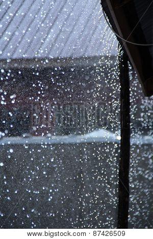 Rain drops falling off a roof