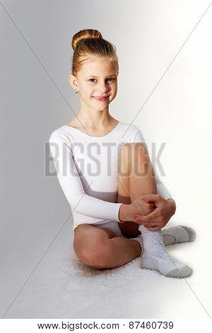 Children Sport. Little Sporty Girl Sitting On The  Carpet Over Grey Background.