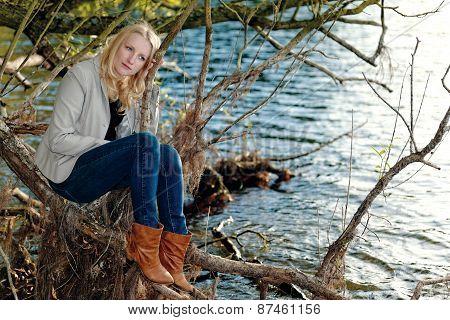Blond melancholic woman sitting by a lake