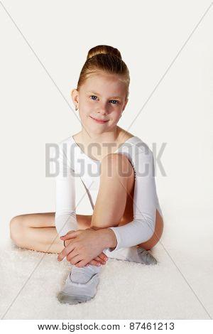 Children Sport. Little Sporty Girl Sitting On The White Carpet.