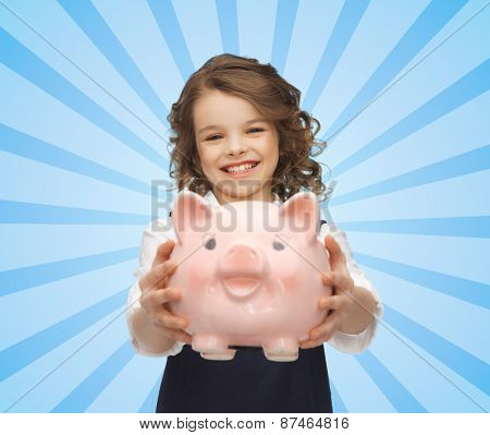 people, money, finances and savings concept - happy girl holding piggy bank over blue burst rays background