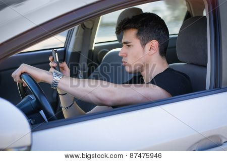 Handsome Young Man Using his Cell Phone Driving a Car