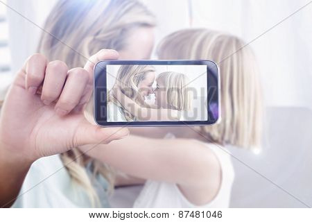 Hand holding smartphone showing against mother and daughter rubbing noses on sofa